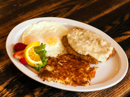 Country-fried steak for breakfast with two eggs and