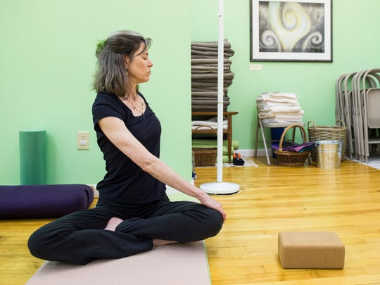 """Julie Aha is the owner of Gettyoga, where she teaches a trauma-informed yoga approach that prioritizes the emotional well-being of those taking the class. """"Yoga helps people have a sense of confidence in their bodies, and that is so important for (victims of domestic violence), where self-esteem is typically very low,"""" Aha said."""
