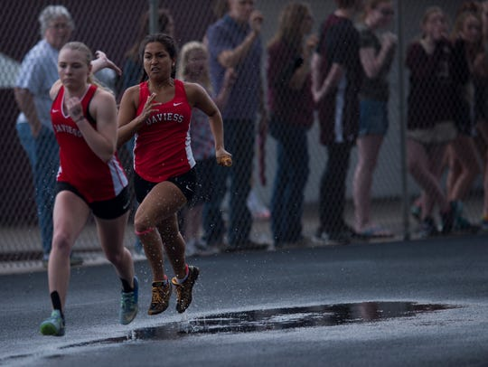 Runners splash through a wet track during a relay race