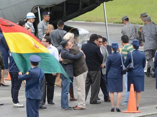 Family members embrace as air force personnel load caskets containing the remains of LaMia flight crew victims into a waiting cargo plane at the military airbase in Rio Negro, Colombia, Friday, Dec. 2, 2016. An honor guard played taps early Friday as members of Colombia's military loaded the five flight crew victims of an air crash that also killed most members of a soccer team and a group of journalists, onto a cargo plane for the trip back to their native Bolivia.