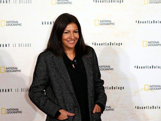 FILE - In this file photo dated Monday Oct. 17, 2016, Paris Mayor Anne Hidalgo poses for photographers during a photo call for the french premiere of the film 'Before the Flood', ('Avant Le Deluge') at Chatelet Theater in Paris. Hidalgo has pushed back at U.S. President Donald Trump for insulting Paris, saying American tourist reservations are up 30 percent in 2017 so far compared to last year.