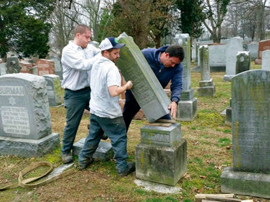 Rosenbloom Monument Co. workers from left, Nathan Fohne, Derek Doolin and Philip Weiss hoist a headstone at the Chesed Shel Emeth Cemetery in University City, Mo., where over 150 headstones were tipped over. The cemetery is getting a show of support from cleanup volunteers, well-wishers and financial contributors from across many faiths.