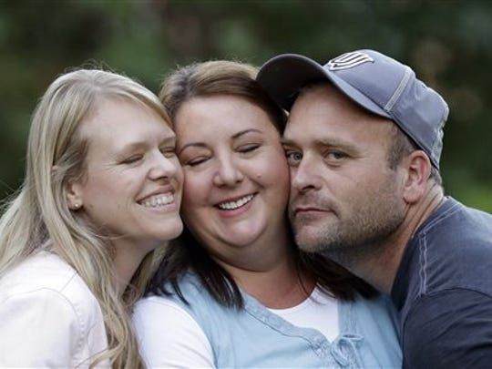 In this file photo, Brady Williams poses with two of his wives, from left to right, Robyn and Rosemary, outside of their home in a polygamous community outside Salt Lake City. Rosemary Williams says she was molested more than two decades ago by her father, Lynn A. Thompson. He is the leader of the one of largest organized polygamy groups in Utah, the Apostolic United Brethren, or AUB.