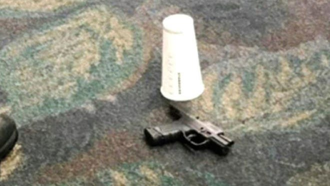This photo taken Friday, Jan. 6, 2017 by passenger Mark Lea and released by Lea Sunday, Jan. 8 shows a handgun which was used by Iraq war veteran Esteban Santiago when he killed five people is seen on the floor at the scene of the attack at the Fort Lauderdale airport in Florida. In a post-9/11 world, American airports have taken all sorts of steps to keep travelers safe. But significant vulnerabilities remain. The attack that killed five people Friday at the Florida airport raised concerns about how to further protect travelers and what place firearms have in U.S. airports. (Mark Lea via AP)