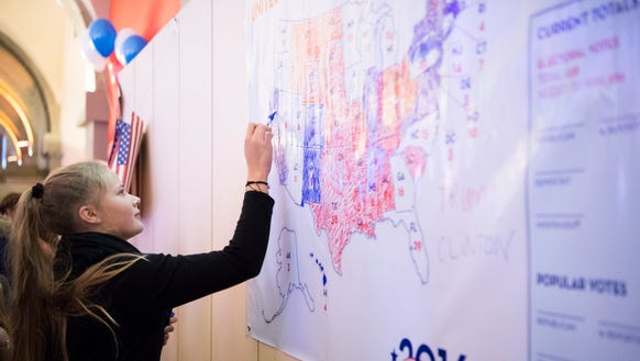 A woman colors in blue for California on a map following