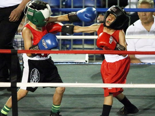 Miguel Montalvo, 10, right, goes up against Moises Rodriguez, 10, in their 61-pound bout during the USA Boxing, Inc. Border Boxing Association Region 8 event Saturday at the County Coliseum. Rodriguez prevailed.