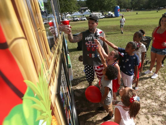 John Hicks buys a round of snow cones for a group of