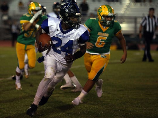 Cathedral City's James Green III carries the ball for a first down against Coachella Valley on Friday, August 25, 2017 in Thermal.