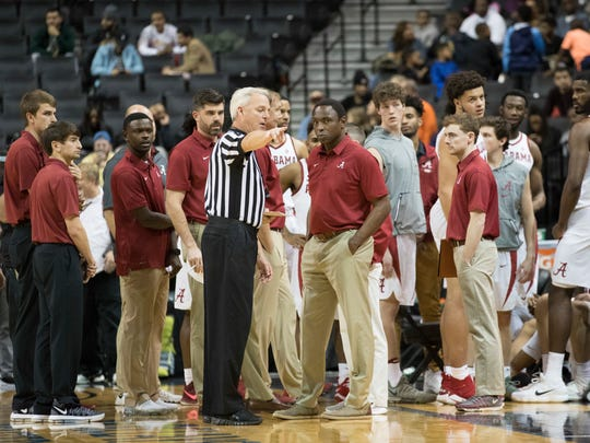 The referee speaks to Alabama head coach Avery Johnson