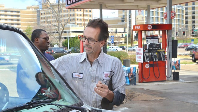Louis Munro (center) replaces an inspection sticker for Durrell McElroy of Jackson Friday at the Texaco gas station at the intersection of North State Street and Woodrow Wilson Avenue in Jackson. The Ward's Wrecker Service station is part of a dying breed of full service gas stations across the nation.