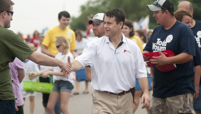 U.S. Rep. Todd Young shakes hands with constituents while walking in the parade during the Greenwood Freedom Festival in 2014.