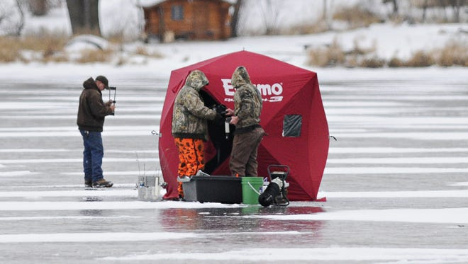 Anglers drills holes in the ice and set up a portable fish house as they settle in on Kraemer Lake in November 2014.