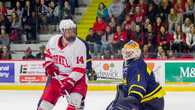 Cornell's Mitch Vanderlaan can't get to a puck over his head in front of Merrimack goalie Colin Delia last season.