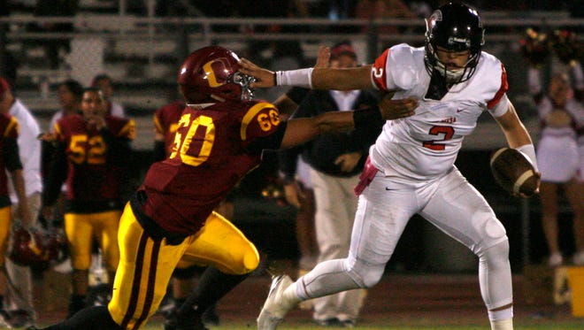 Rio Mesa High quarterback Austin Maciel (right) tries unsuccessfully to fend off the sack by Oxnard defensive end Mark Argueta in Friday's game.