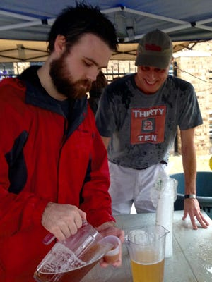 Justin Bailey and Edan Moran serve their home brews from a shared tent Saturday at Funktoberfest at Spirits Food & Friends in Alexandria.