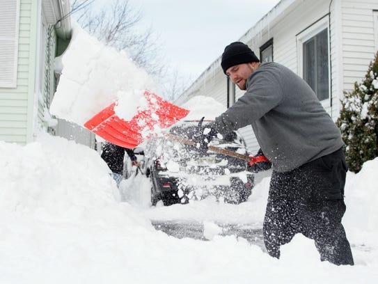 Dan Dubrow, 23, of Shrewsbury, shovels snow from his