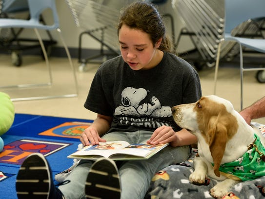 """Chancey Cogley, 10, reads to """"Poppy"""" March 17 during the Pet Partners: Read With Me session at the Tryon Branch Library. Pet Partners:Read With Me is a special initiative to promote literacy and instill a lifelong love of reading by having children read to therapy animals on Saturdays."""