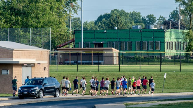 Dunlap High School boys cross country runners head out for a warmup at the start of practice Tuesday, Aug. 11, 2020 at the school.