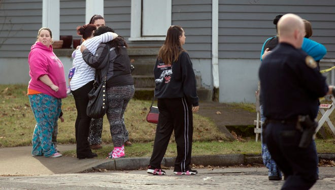Family members embrace their children, who were escorted out of Rosemary Anderson High School in North Portland after a shooting Dec. 12.