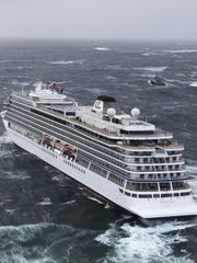 In this image taken from video made available by CHC helicopters, helicopters fly over the cruise ship Viking Sky after it sent out a Mayday signal because of engine failure in windy conditions off the west coast of Norway, Saturday March 23, 2019. A cruise ship with engine problems sent a mayday call off Norway's western coast on Saturday, then began evacuating its 1,300 passengers and crew amid stormy seas and heavy winds in a high-risk helicopter rescue operation.