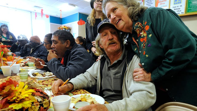 Martha Brown gives a hug to Dewey McCort after he gets his meal during the Day Before Thanksgiving Breakfast on Wednesday, Nov. 23, 2016, at City Light Community Ministries.