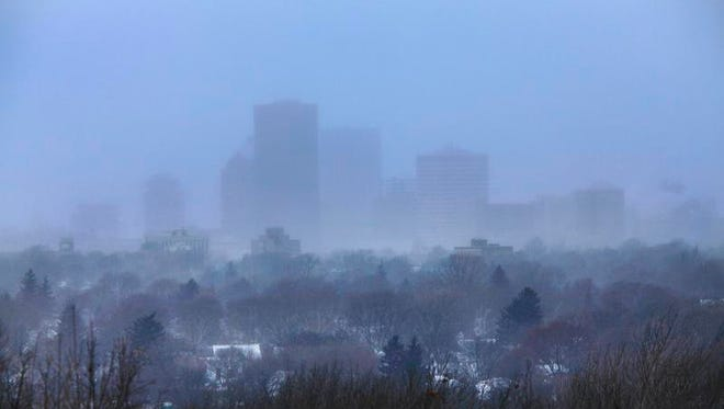 Downtown covered in frigid blowing snow earlier this month, as seen from Cobbs Hill.