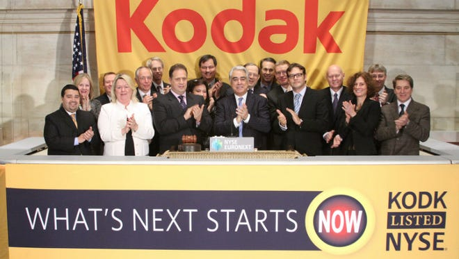 Kodak officials, including Antonio Perez, center, ring the opening ball at the New York Stock Exchange on Wednesday.