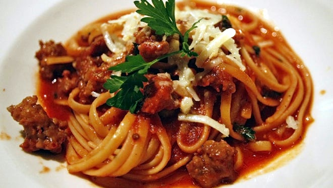 Linguini served with marinara sauce and sweet Italian sausage topped with parsley, deglazed with red wine and garlic is one of the entrees served the Drunken Cook, Family Style Italian Restaurant.