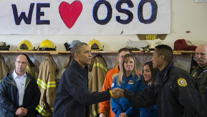 US President Barack Obama (2L) shakes hands with first responders after delivering remarks at the firehouse in Oso, Washington, April 22, 2014, after touring the devastation left by a recent mudslide.