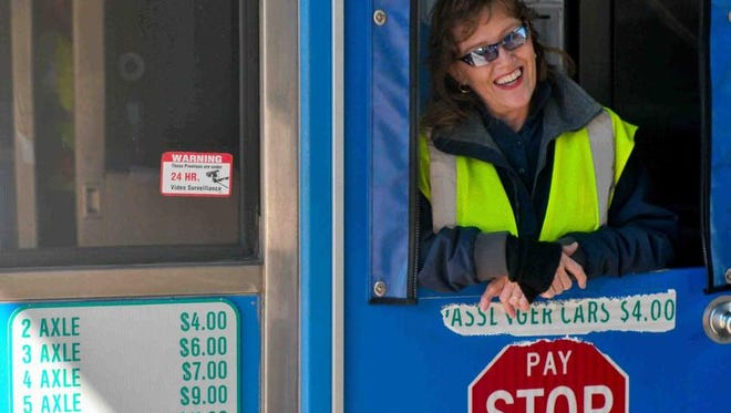 Deborah Cooper, of Elkton, Md., collects tolls from motorists at the Newark Toll Plaza Wednesday. Cooper has been working at the toll plaza for roughly 28 years. Her father, Joseph Rybicki, Sr., collected the plaza's first toll in 1963.