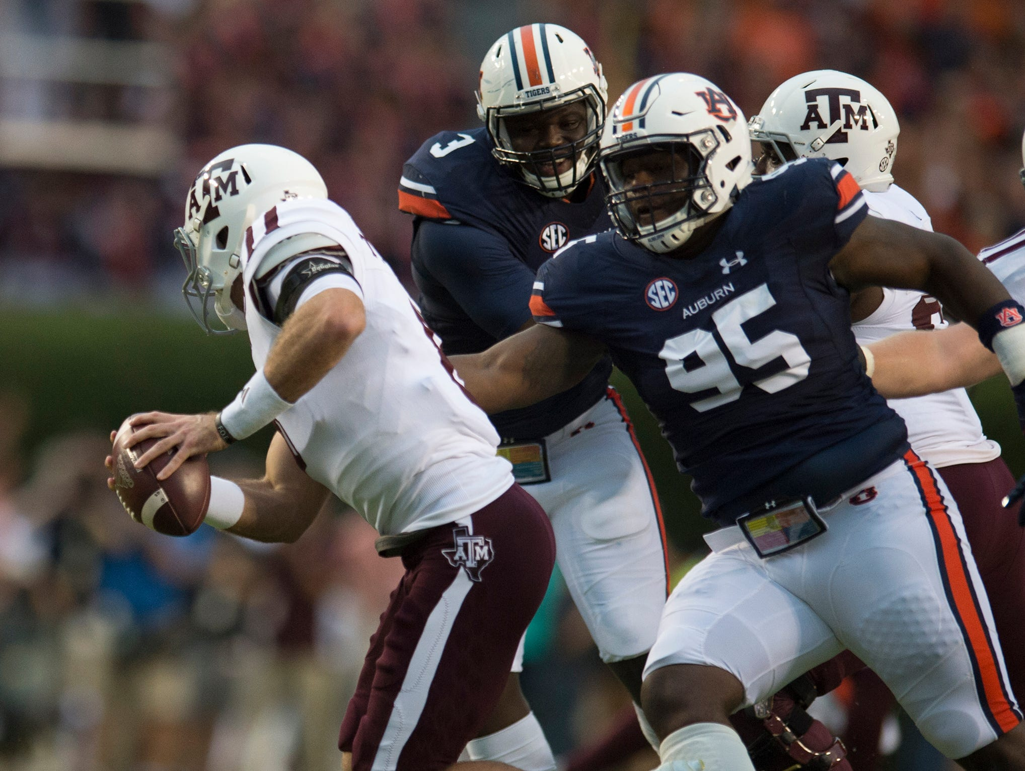 Auburn defensive lineman Dontavius Russell (95) attempts to tackle Texas A&M quarterback Trevor Knight (8) runs away from him during the Auburn vs. Texas A&M NCAA football game on Saturday, Sept. 17, 2016, at Jordan Hare Stadium in Auburn, Ala. Albert Cesare / Advertiser