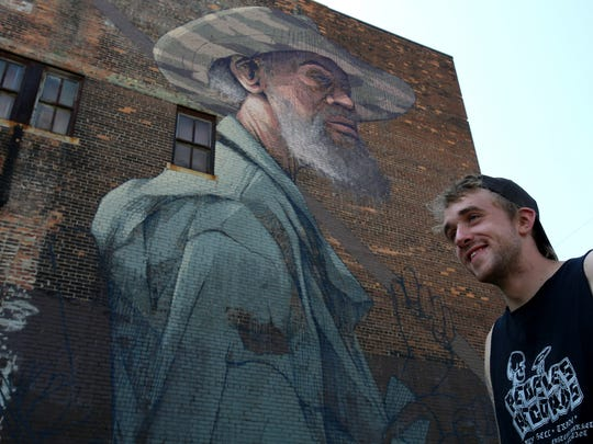 Pat Perry stands beside the four story tall mural he is painting at Mitchell and Gratiot Avenue.
