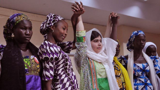 FILE-In this file photo taken Monday, July 14, 2014, Pakistani activist Malala Yousafzai, center, raises her hands with some of the escaped kidnapped school girls of government secondary school Chibok, during a news conference, in Abuja, Nigeria. On the first anniversary of the mass kidnapping by Islamic extremists of hundreds of girls from a school in northeast Nigeria, President-elect Muhammadu Buhari said he cannot promise to find the 219 who are still missing. (AP Photo/Olamikan Gbemiga, file)