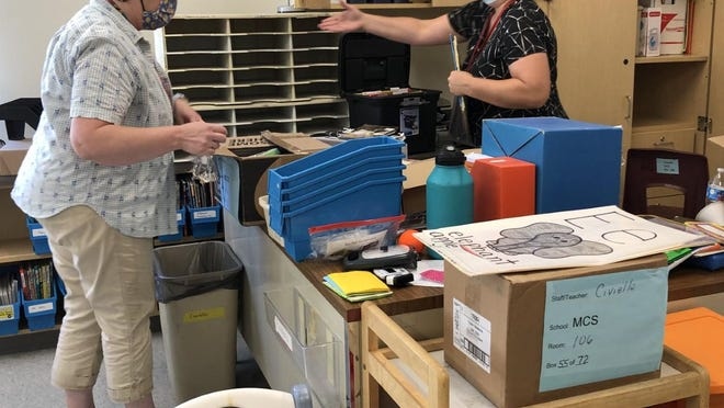 Donned in masks, teacher Nicole Civiello, right, and education technician Donna Goodrich prepare their classroom for the coming school year at the newly expanded and renovated Margaret Chase Smith Elementary School on Wednesday.