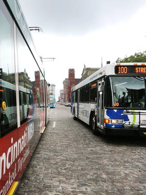 A Metro bus drives alongside the streetcar in Over-the-Rhine last fall.