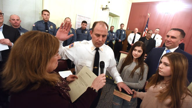 Mayor Dianne Didio swears in  Capt. William Wicker as the new Oradell chief of police. Daughters Gianna (12)  and Gabriella (10) hold the Bible while his brother, Det. Lt. Keith Wicker, looks on.