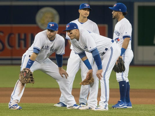 Toronto Blue Jays infielders, from left, Justin Smoak, Troy Tulowitzki, Darwin Barney and Devon Travis wait for a pitching change during the seventh inning of a baseball game against the Baltimore Orioles in Toronto on Friday April 14, 2017.  (Fred Thornhill/The Canadian Press via AP)