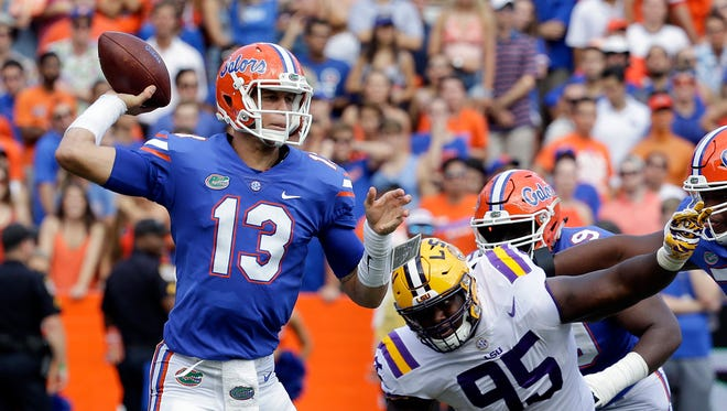 Florida quarterback Feleipe Franks (13) throws a pass as he is pressured by LSU nose tackle Ed Alexander (95) during the first half of an NCAA college football game, Saturday, Oct. 7, 2017, in Gainesville, Fla.