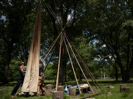 From left, Two Clouds, of the Ramapough Lenape Nation, and Ohitika Naji, from South Dakota and a member of the Lakota, put up a tepee at Split Rock Sweetwater Prayer Camp in Mahwah in May.