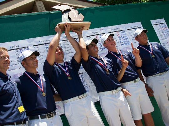 The DeWitt High School golf team hold their Div. 2 State Championship trophy Saturday at Forest Akers in East Lansing.