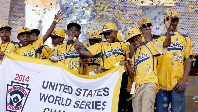 In this Aug. 27, 2014, file photo, members of the Jackie Robinson West Little League baseball team participate in a rally celebrating the team's U.S. Little League Championship in Chicago. Little League International has stripped Chicago's Jackie Robinson West team of its national title after finding the team falsified its boundary map. The league made the announcement Wednesday morning, Feb. 11, 2015, saying the Chicago team violated regulations by placing players on the team who didn't qualify because they lived outside the team's boundaries. Little League International also suspended Jackie Robinson West manager Darold Butler from league activity.