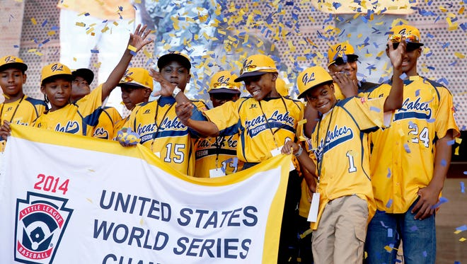In this Aug. 27, 2014, file photo, members of the Jackie Robinson West All Stars Little League baseball team participate in a rally in Chicago celebrating the team's U.S. Little League Championship. In a lawsuit filed Thursday, Feb. 11, 2016, in Chicago's Cook County Circuit Court, the parents of 13 members of the Chicago Little League team stripped last year of its 2014 U.S. championship are suing team officials, Little League Baseball, an ESPN sportscaster and the man who exposed the team's residency violations.