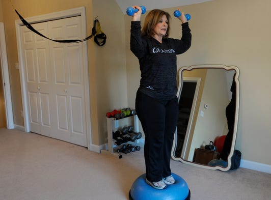 Teresa Sawyer balances on a BOSU Balance Trainer while lifting weights. Sawyer retired early from her job as a music and theater teacher to become a personal trainer.