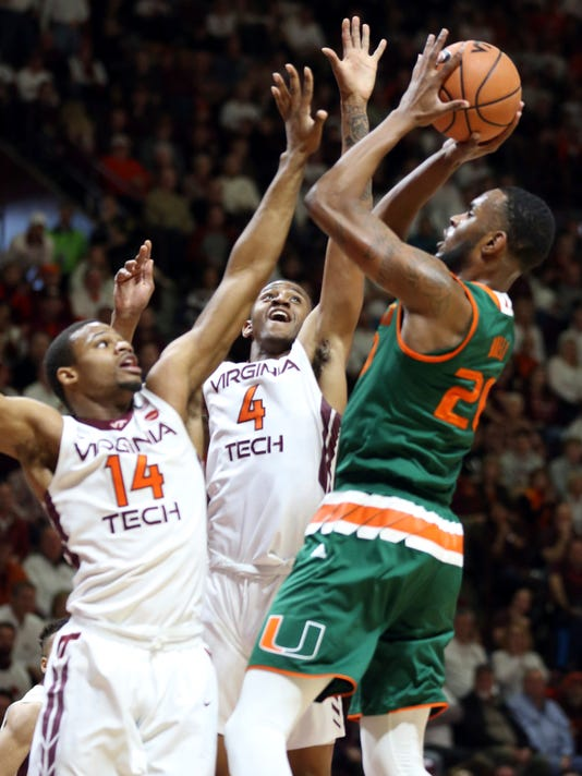 Miami's Dewan Huell (20) has his shot contested by Virginia Tech's P.J. Horne (14) and Nickeil Alexander-Walker (4) during the first half of an NCAA college basketball game in Blacksburg, Va., Saturday Feb. 3 2018. (Matt Gentry/The Roanoke Times via AP)