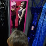 Alondra Cordova tries on a dress with the help of Kelli Smith, left, as Jeanne Barr looks on at the Cinderella Project event where girls were able to pick out a free dress for their prom.