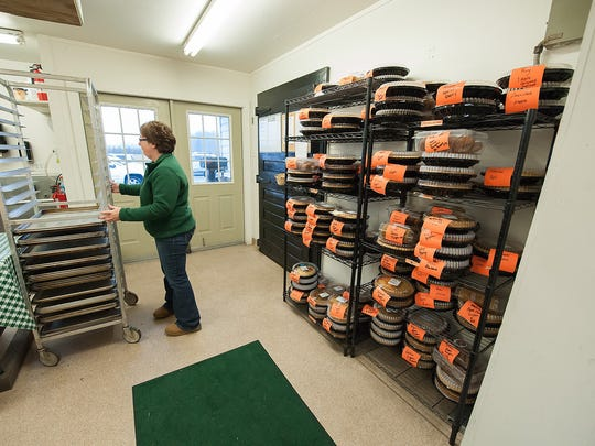 Connie Warren, an employee at Fifer Orchards in Camden-Wyoming, prepares turkey and pie orders Wednesday.