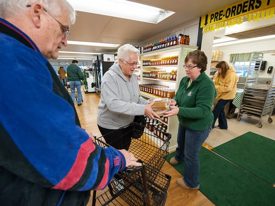 Fifer Orchards employee Connie Warren (right) hands an apple pie and pumpkin roll to Deborah and Bob Beatty of Florida at Fifer Orchards in Camden-Wyoming on Wednesday. The Beattys were spending Thanksgiving with their son, who is stationed at Dover Air Force Base.