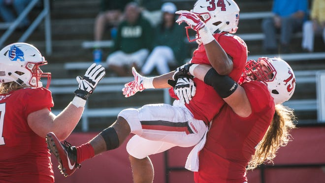 Ball State's James Gilbert celebrates with Vinnie Palazeti, right, and Kaleb Slaven against UAB in the home opener on Sept. 9 at Scheumann Stadium.