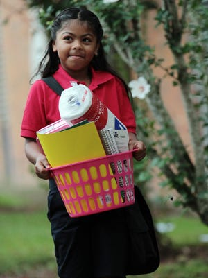 Brittney Garcia, 7, carries a basket of school supplies as she arrives for her first day of second grade Tuesday, August 12, 2014, at J.W. Faulk Elementary in Lafayette, La.