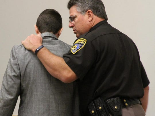 Livingston County Sheriff's Deputy Dave DeVries speaks to convicted murderer Anthony Sean Duke as the latter is led out of a Howell courtroom Thursday afternoon following the verdict.